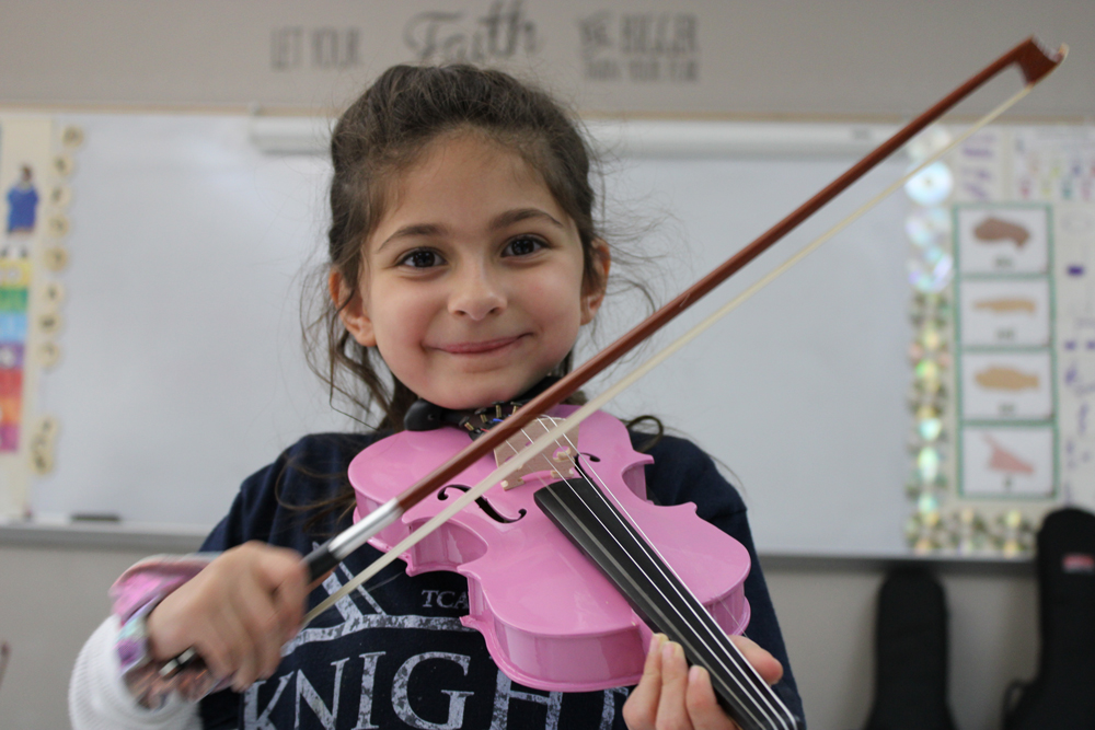 Little girl playing pink violin