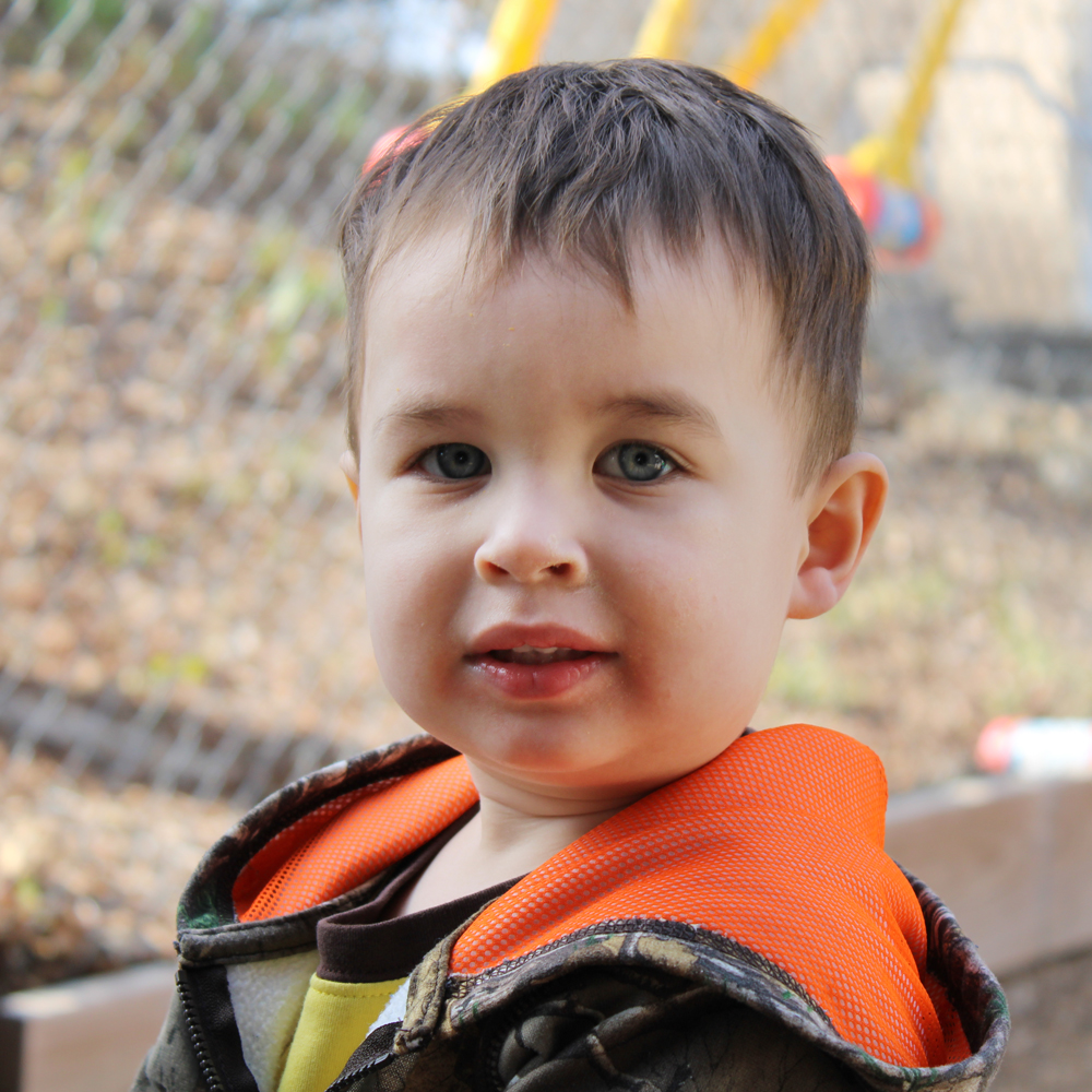 little boy in playground looking at camera