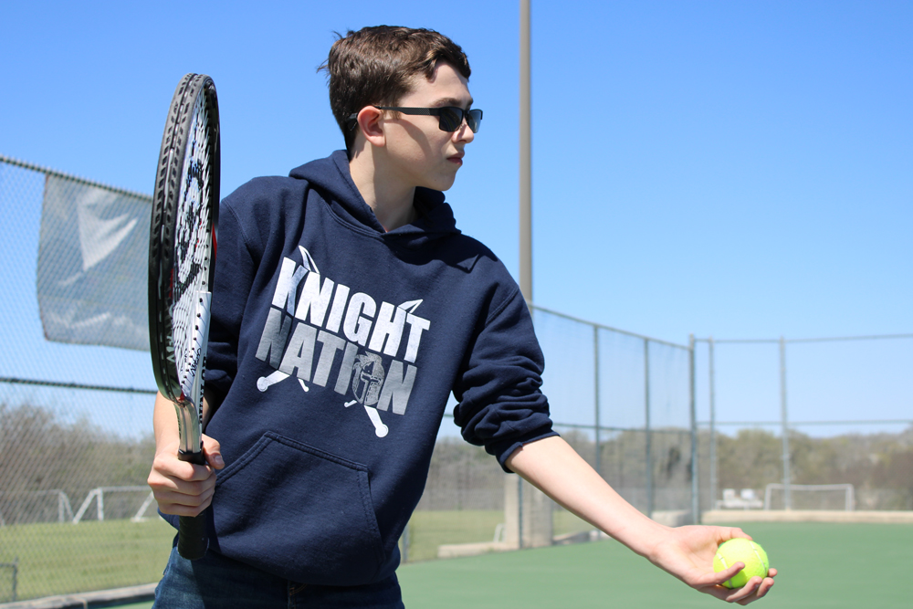 boy in sweatshirt and sunglasses about to serve in tennis match