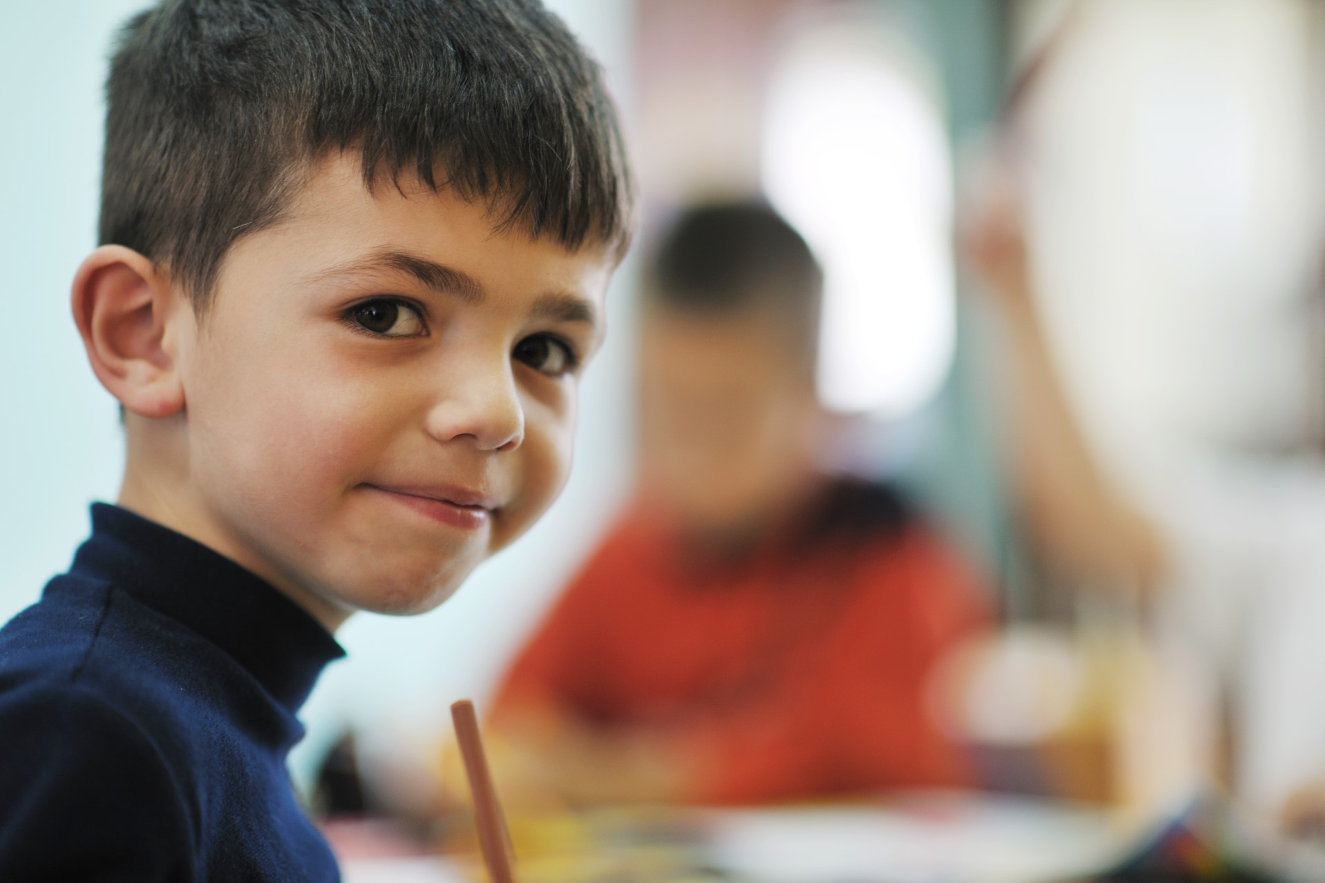 little boy in classroom looking at camera